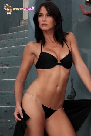 Maillot Noir 2 Pièces avec String pour Travesti - Maillot 2 pièces pour travesti avec un string en lycra noir, réglable avec sa ceinture bijou. Un bikini sexy et sophistiqué à porter dans ou en dehors de l'eau.